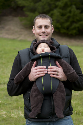 Father with a front baby carrier, holding his newborn son in a cute little pouch in front of his chest